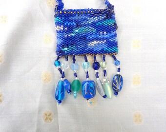 Blue ocean inspired amulet bag of glass beads of various styles in ocean wave colors, handmade.