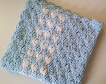 Blue and white crochet baby blanket in the Catherine Wheel pattern.