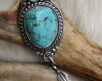 turquoise pendant in sterling  silver  with feather and bear paw on a chain