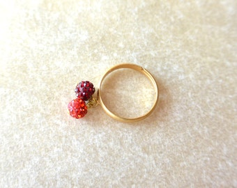 Gold adjustable Ring with 2 balls of red strass.