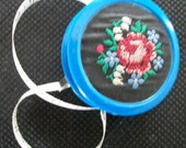 Vintage - ROLLUP CELLULOID TAPE- Fabric Rose & Lily of the Valley Embroidered- back plain  with red button to roll up- very good condition