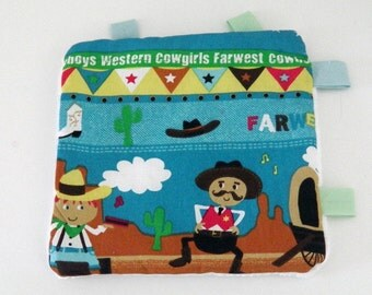 Taggie blanket  in coton fabric  with western and cowboys and white fleece.