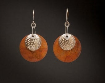 A silver textured dome fronts these patinaed copper disks. These richly colored earrings are lightweight and slightly musical.