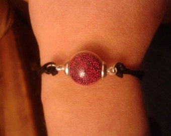 Bracelet with glass globe filled with micro-beads pink fushia and black