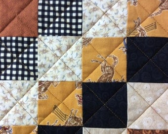 Quilted table runner with western motif and earthy tone fabrics.