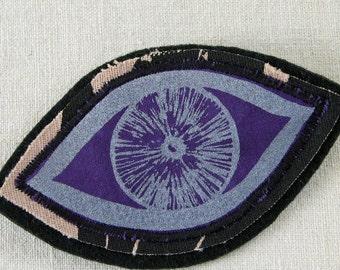 Eye brooch pin, fabric brooch pin, screenprinted eye design, silver eye, purple and black, open eye motif, all seeing eye, coat accessory