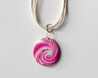 Pink and white Swirled Pendant on a white mulistranded necklace