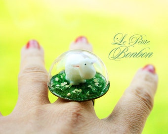Little sheep is inside the dome playing on the grass glass globe ring