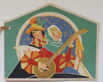 Art Deco vintage Christmas bridge tally card with madrigal minstrel singers carolers with gold and red tassel ephemera