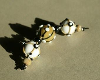 Handmade lampwork bead set in white beige and black by Flamejewels.