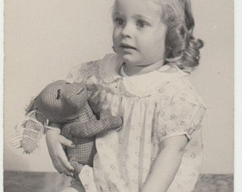 Vintage/Antique side view photo of a beautiful little girl holding her stuffed toy bunny