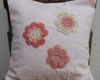 Tender pink linen cushion cover with three pink flower doilies