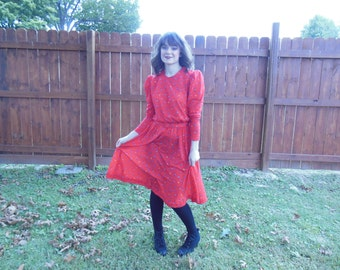 Vintage 1950's red, floral pattern dress with ruffled sleeves and button detail.