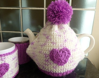 Hand crocheted cream and purple tea cosy / cozy with purple pom-pom and heart