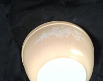 Vintage Yellow Pyrex bowl with white raised floral pattern on front and back.