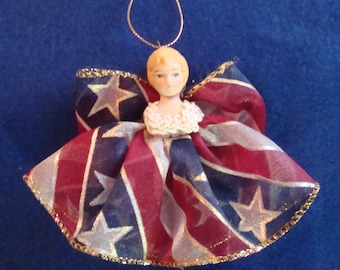 Hope Angel ornament has a porcelain head and dress and wings are patriotic ribbon