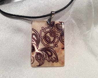 Mother of pearl shell pendant with oriental henna design. 1.5. X 2 inch rectangle.