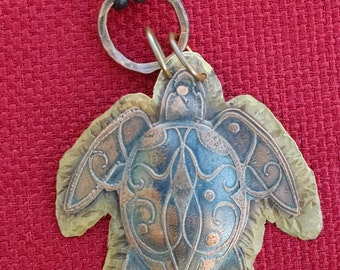 Etched copper sea turtle riveted to brass base with leather cord and S clasp