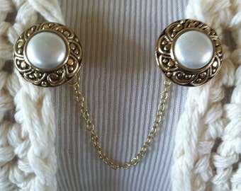 The mattie gold tone round pearl sweater clip adds a touch of elegance to your cover ups.