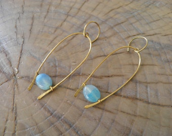 "Earrings... ""Suspended"" earrings are a beautiful blue hemimorphite stone caught in hammered brass wire."