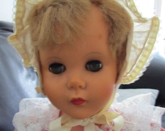 Vintage,29 inches tall, cute, cuddly little doll with a beautiful pink printed cotton and lace dress