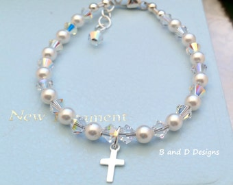 Swarovski  pearl bracelet made with white pearls, clear ab crystals and accentuated with a silver cross. Perfect fir your little girl!