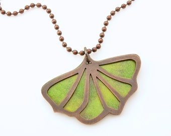 Handmade reversible enameled pendant; copper gingko leaf silhouette with reversible enameled background of spring green or autumn yellow.