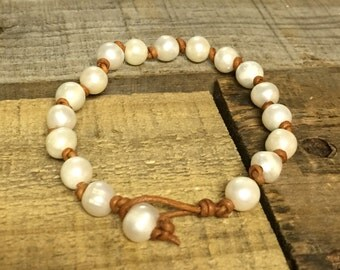 Beautiful fresh water pearl bracelet hand knotted on distressed brown leather cord.  Measures 7.5""