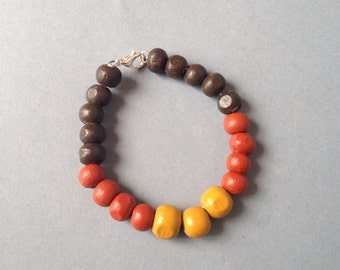 Bracelet adorned with crude wood round beads, hand painted.