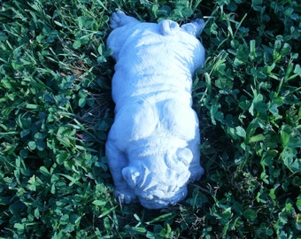 Concrete statue of laying pug
