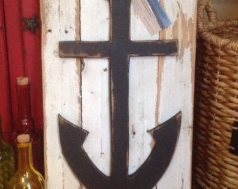 Rustic black anchor on worn white fencing background