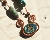 Wire-wrapped necklace with bird bead, copper wire and stones