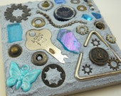 small found object mosaic on 4 inch tile, rusty hardware with turquoise and sapphire colored bits on baby blue grout
