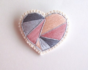 Valentines day heart brooch hand embroidered with geometric color block shapes in light and dark grays pink and dusty rose on cream muslin