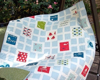 Nautical Lap Quilt in Red, White, Blue, Lime Green, Deep Teal on a blue and cream background.