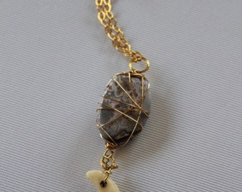 Gold chain necklace with a wire wrapped pendant and tooth