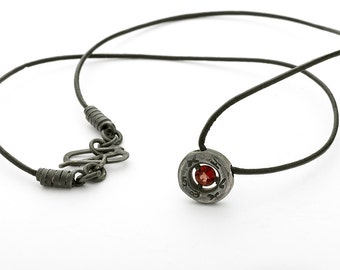 Silver pendant with a garnet.