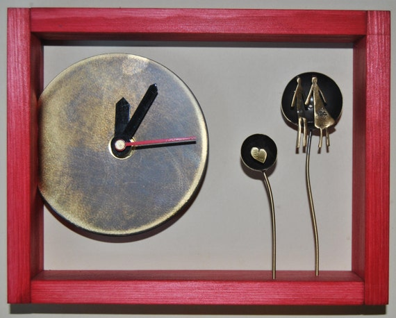 Deep red wooden clock with two flowers and a couple.