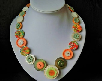 """Pumpkin Patch is a unique, handmade button necklace, 19"""" (48 cm) long, with  35 orange, green and cream buttons threaded onto wire."""