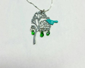 Blue bird in tree necklace with green teardrop leaves