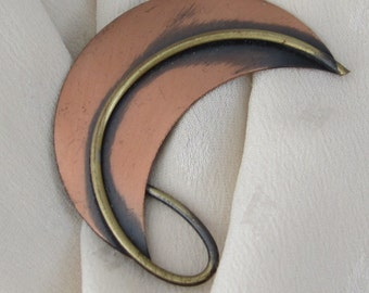 Vintage burnished copper & brass pin/brooch circa 1960s -1970s. Design is a  modernistic crescent moon shape with a brass swoosh overlay.