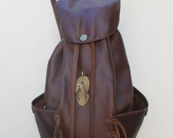 Handmade molasses bovine leather backpack with two side pockets and fringing. Lining and inside zip