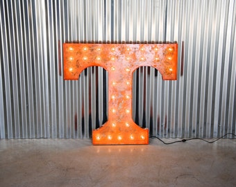 "UT Power ""T"" weathered metal letter light in distinctive UT orange with globe ""Marquee"" style bulbs."