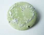 hand embroidery white heart brooch on printed green cotton with sequins and silver highlights.