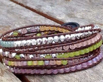 Five time wrap around bracelet of Japanese seed beads, multifaceted metal and glass beads in matte shades of green and pinks.