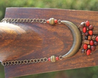 Ethnic necklace in seeds, wood and coral, put on a splendid bronze connector