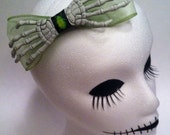 One huge green skeleton hand hair bow. Portion of sale goes to charity.