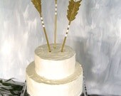 The Archer arrow cake topper decoration shown in gold and white with glitter