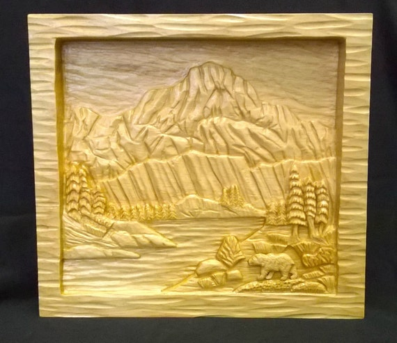 Mountain lake relief carving with bear on white pine