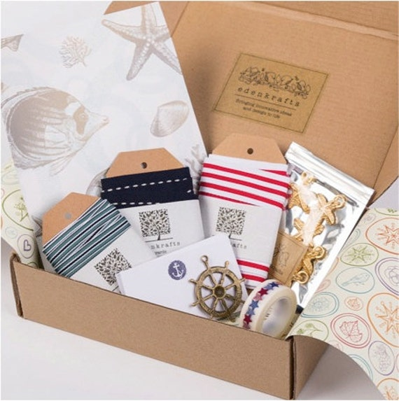 A curated + nautical themed craft box of unique, high quality craft supplies - striped ribbon, starfish embellishments, pendant, notecards